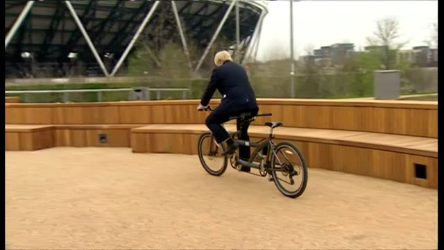 Exterior shots of Boris Johnson riding tandem bicycle bike around Queen Elizabeth Olympic Park with ArcelorMittal Orbit Sculpture in background...