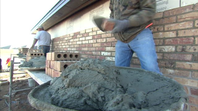 Exterior shots of bricklayers at work building a house scooping up wet cement and laying bricks on December 19 2014 in Midland Texas
