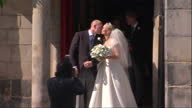 Exterior shots of Bride and Groom Mike Tindall Zara Phillips kiss at Canongate Kirk church walk out of the church followed by best man bridesmaids...