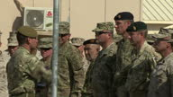 Exterior shots of British American and Afghan soldiers taking part in ceremonial flag lowering ceremony to mark the handover of Camp Bastion to...