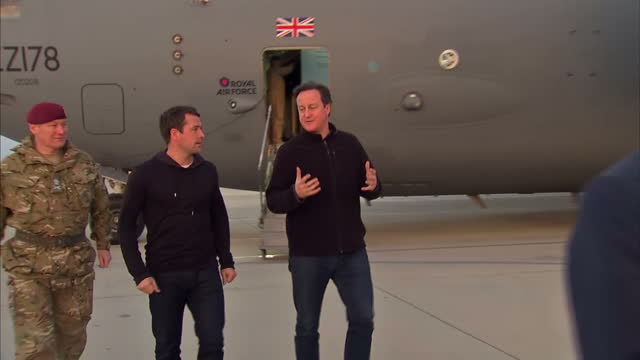 Exterior shots of British Prime Minister David Cameron and former England footballer Michael Owen stepping down from RAF transport plane and greeting...