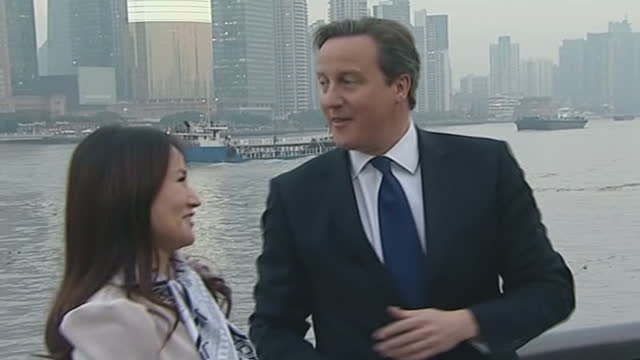 Exterior shots of British Prime Minister David Cameron chatting with Rekoo vice president Lisa Pan at the Bund waterfront area on the Huangpu River...