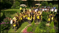 Exterior shots of British Prime Minister meeting Girl Brownies and their leaders and standing with the girls around the 'Big Brownie Birthday cake'