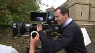 Exterior shots of Chancellor George Osborne MP talking to camera cew on the production set of Agatha Raisin and using film camera on August 20 2015...