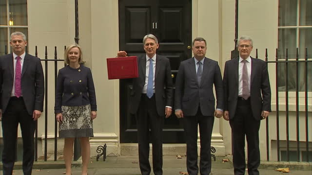 Exterior shots of Chancellor Philip Hammond walking out of Number 11 Downing Street and posing with the red Budget box on November 22 2017 in London...