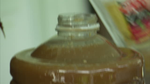 Exterior shots of containers of heavily polluted brown water being handled and poured from one container to another to demonstrate levels of...