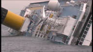 Exterior shots of Costa Concordia in ocean sea with rescue team boats positioned around ship laying on its side in water Costa Concordia cruise ship...