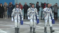 Exterior shots of crew of Soyuz Mission TMA19M Tim Peake Commander Yuri Malenchenko Timothy Kopra walk out of building and stand in a line before...