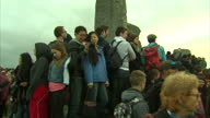 Exterior shots of crowds at Stonehenge during Summer solstice celebrations some perched on and around the stones and many taking pictures with...