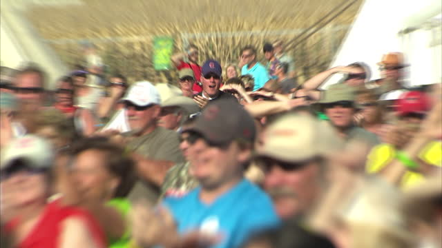 Exterior shots of crowds of country music fans cheering and clapping some wearing Tshirts protesting against the Keystone XL Pipeline project during...