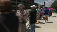 Exterior shots of crowds of people queueing outside the Big Sandy Arena before the start of a rally by President Trump many people sheltering from...