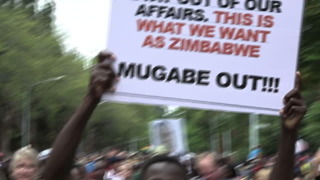 Exterior shots of crowds of protesters marching along a road holding up signs and newspaper pages with antiMugabe slogans and waving Zimbabwean flags...