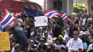 Exterior shots of crowds of protesters on the streets of Bangkok blowing whistles and waving flags calling for Prime Minister Yingluck Shinawatra to...