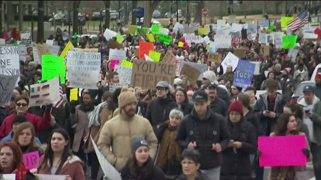 Exterior shots of crowds of protesters with placards protesting against the temporary travel ban on people from seven mainly Muslim countries on...