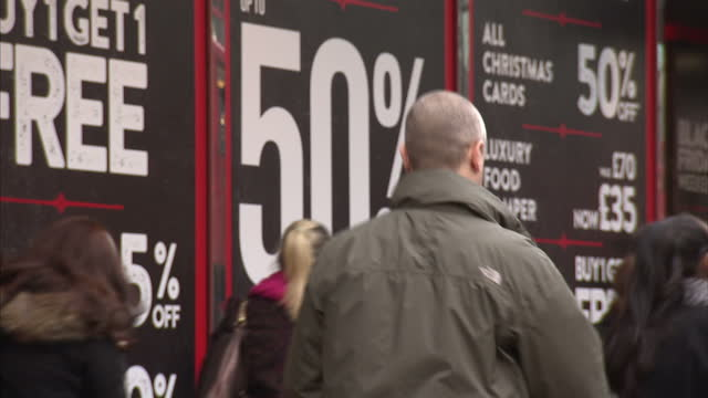 Exterior shots of crowds of shoppers passing a branch of BHS on Oxford Street with large signs in the windows advertising Black Friday deals >> on...