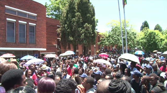 Exterior shots of crowds of students gathered outside the University of Zimbabwe singing chanting slogans and holding signs calling for the return of...