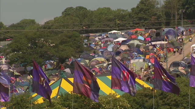 Exterior shots of crowds of tents pitched in a field and people arriving at a campsite at Glastonbury Festival>> on June 23 2010 in Pilton England