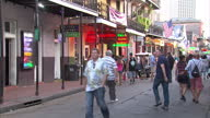 Exterior shots of crowds of tourists walking along and near Bourbon Street in the French Quarter of New Orleans past various brightly neon lit bars...