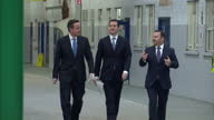 Exterior shots of David Cameron and George Osborne walking into the Bombardier train workshops to greet employees on February 12 2015 in Derby England