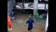 Exterior shots of debris and destruction in Phuket in the aftermath of the Tsunami including shots of search and rescue workers searching a flooded...