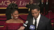 Exterior shots of Denzel Washington speaking to reporters on the Oscars red carpet accompanied by his wife Pauletta joking 'You didn't see that' as...