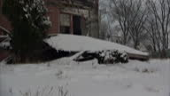 Exterior shots of derelict houses on a Detroit street as cars drive along in snow on January 20 2015 in Detroit Michigan