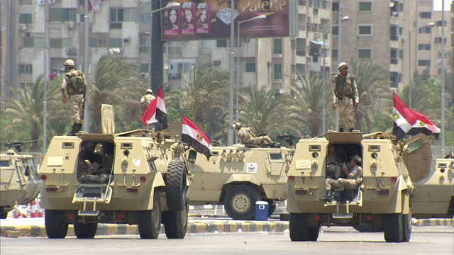 Exterior shots of Egyptian Army on the streets of Cairo sitting next to Army vehicles and single lone Pro Morsi supporter holding up picture within...