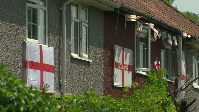 exterior shots of England flags St George's crosses adorning houses supporting the team in the World Cup Exterior shots of England flag flying from...