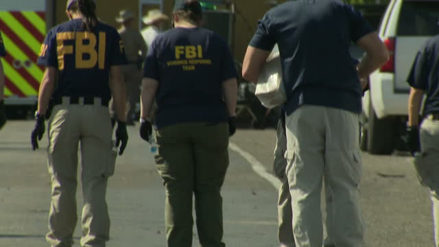 Exterior shots of FBI personnel examining the road and collective evidence outside the First Baptist Church of Sutherland Springs where 26 people...
