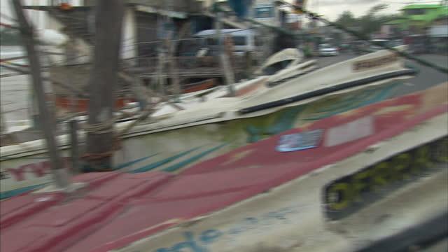 Exterior shots of fishing boats fishermen and a main road in Katugoda Sri Lanka on December 26 2014 in Galle Sri Lanka