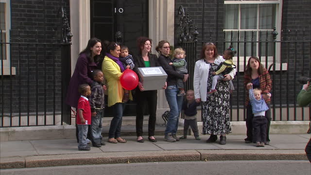 Exterior shots of five mothers posing outside Downing Street with a petition opposing cuts to Sure Start Children's Centres Mothers Protest Against...