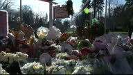 Exterior shots of flowers and messages left in tributes memory of victims of Sandy Hook School shooting with teddy bears and messages written on...