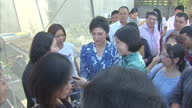 Exterior shots of former Thai PM Yingluck Shinawatra posing for photos with supporters whilst showing off her vegetable garden on February 12 2016 in...