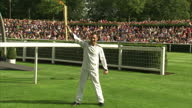 Exterior shots of Frankie Dettori with the Olympic Torch performs his flying dismount from former race horse Monsignor lights Olympic torch held by...