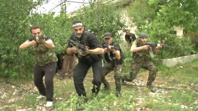 Exterior shots of FSA rebels advancing through Latakia province firing arms chanting as they advance FSA Rebels in Syria on June 24 2012 in Syria