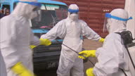 Exterior shots of health workers or volunteers in hazmat overalls and protective masks gloves etc spraying each other with disinfectant and walking...