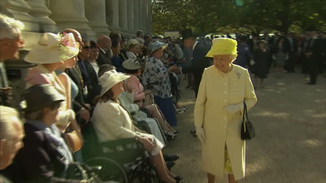 exterior shots of Her Majesty Queen Elizabeth II wearing a canary yellow jacket and hat meeting elderly and disabled guests in wheelchairs at Royal...