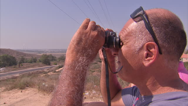 Exterior shots of Israeli civilians stood on hill overlooking Gaza with binoculars on July 29 2014 in Sderot Israel