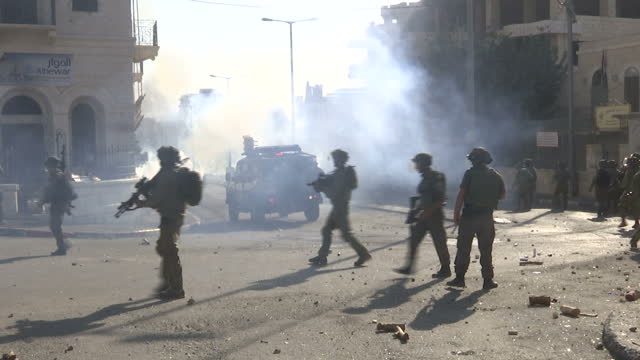 Exterior shots of Israeli police and IDF soldiers firing tear gas rounds towards stone throwing Palestinian protesters in Bethlehem with loud...