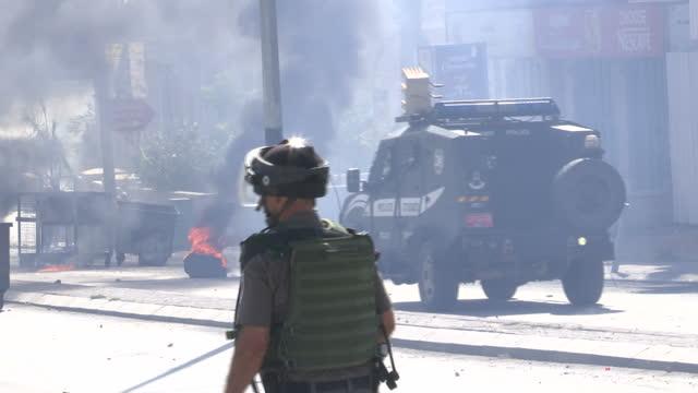 Exterior shots of Israeli soldiers firing tear gas towards rioting Palestinians in Bethlehem as bonfires burn in the street on October 17 2015 in...