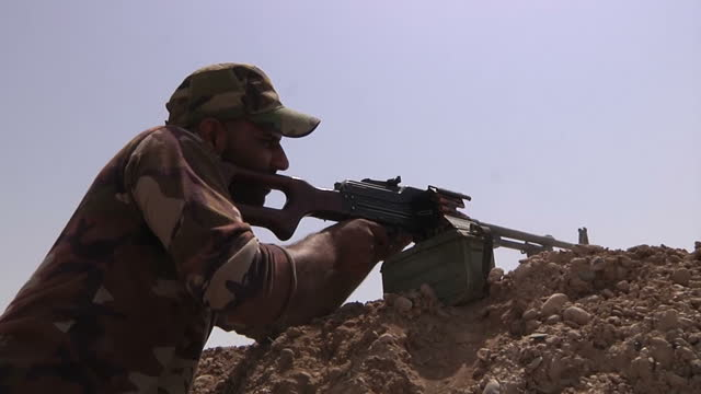 Exterior shots of Kurdish Peshmerga fighters gathered near Naqshbandi with one fighter firing a gun over the top of an earth rampart>> on August 15...