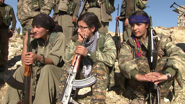 Exterior shots of Kurdish Peshmerga troops Yazidi volunteer fighters stood on a mountain overlooking Sinjar at military bases holding Kurdish flags...