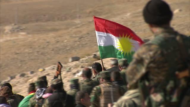 Exterior shots of Kurdish Peshmerga troops Yazidi volunteer fighters walk down Sinjar mountain overlooking Sinjar town and holding Kurdish flags on...