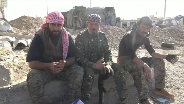 Exterior shots of Kurdish YPG soldiers sat around Humvees next to rubble and damaged buildings in Raqqa on 17 October 2017 in Raqqa Syria
