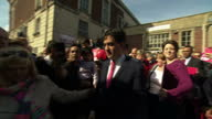 Exterior shots of Labour leader Ed Miliband leaving a building in Barry and boarding the Labour battlebus waving to supporters one of whom takes a...