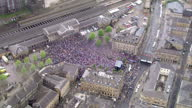 Exterior shots of large crowds in the centre of Huddersfield town and the football team on a makeshift stage celebrating the team's promotion to the...