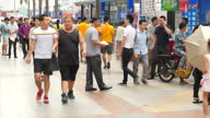 Exterior shots of large crowds of people in a busy shopping area walking around and using their mobile phones to text and talk on September 20 2015...