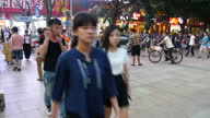 Exterior shots of large crowds of shppers in Shenzhen passing a number of electronic shops and traffic driving down busy roads on September 20 2015...