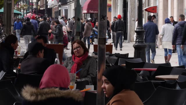 Exterior shots of large numbers of people sitting at outdoor cafes and walking along the Avenue Habib Bourguiba>> on March 06 2015 in Tunis Tunisia
