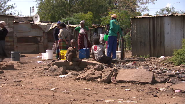 Exterior shots of life in a Soweto slum with people collecting water in buckets General scenes of life in a Soweto township and the studios of 702...